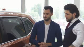 Handsome young man discussing a new automobile for sale with his friend while shopping for a car at the dealership showroom. Male friends choosing automobiles.