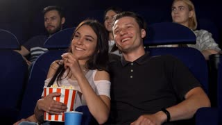 Handsome young man hugging his beautiful girlfriend while watching a movie together at the cinema. Cheerful young loving couple enjoying movie premiere, eating popcorn. Lifestyle concept.