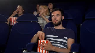 Handsome young man smiling joyfully showing thumbs up, while watching film premiere at the local movie theatre. Attractive male spectator enjoying movies at the cinema.