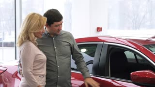 Happy beautiful mature couple smiling to the camera while choosing a new auto at the dealership. Mature man buying a car for his beautiful wife consumerism travel transport automotive