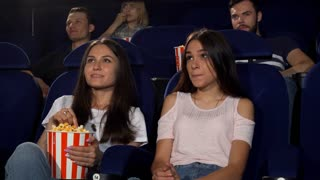 Happy female friends eating popcorn, while watching a movie together at the cinema. People enjoying new film premiere at the movie theatre. Friendship, entertainment, leisure concept.