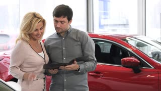 Happy mature couple choosing a new car to buy husband and wife reading booklet at the dealership salon consumerism buying automotive retail rental choice purchase travel driving
