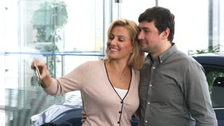 Happy mature couple laughing taking selfies while shopping for a new car together at the dealership family love relationships couples buying retail rental travel consumerism smart phone mobile