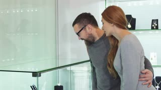 Mature bearded man embracing his beautiful wife while choosing jewelry together at the boutique love relationships people anniversary consumerism shopping buying customers