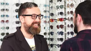 Mature bearded man shopping for eyewear talking to a professional optometrist at the opticians store. Helpful optometrist assisting his male customer in choosing new glasses communication buying.