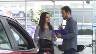 Mature bearded professional salesman working at the car dealership. Car dealer helping his female customer choosing a new automobile. Buying, communication, discount, advising.