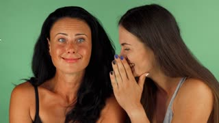 Mature beautiful woman laughing while her younger friend whispering secrets to her ear. Cheerful female friends gossiping on green chromakey background. Friendship, lifestyle concept.