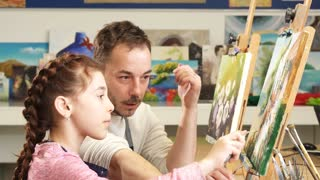 Mature male painter artist enjoying working on a painting with his cute little daughter at the art workshop. Adorable little girl painting a picture with her father family love lifestyle parenting