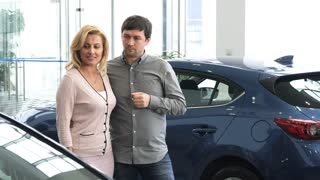 Mature man and his beautiful happy wife discussing cars at the dealership choosing new auto to buy buying shopping customers purchasing consumerism family travelling marriage lifestyle