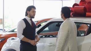 Mature man choosing a new automobile at the car dealership. Professional auto dealer opening door of an automobile for his client. Man getting inside a new car at. Sales, purchase, service.