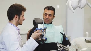 Mature man having medical appointment at the clinic professional dentist showing dental mold to his patient healthcare medicine profession occupation job dentistry professionalism