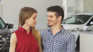 Portrait of a handsome man and his gorgeous girlfriend smiling happily embracing showing car keys to the camera, posing at the dealership showroom. Consumerism, driving, ownership.