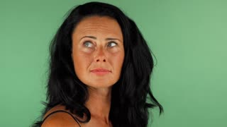Portrait of a stunning mature happy woman smiling looking away. Gorgeous dark haired woman looking surprised posing on chromakey background. Emotions, happiness, wellbeing concept.