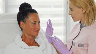 Professional beautician holding syringe with face fillers, examining face of her female client. Mature beautiful woman getting facial injections at beauty clinic. Anti-aging revitalization concept.