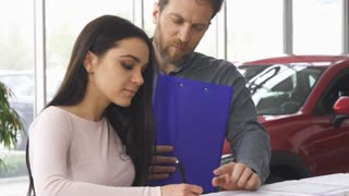 Professional car salesman helping his female client signing papers after buying a new car at the dealership showroom. Beautiful woman filling documents for her newly bought auto.