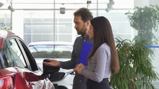 Professional salesman talking to a young woman at the car dealership salon. Female customer choosing a new automobile at the showroom. Mature auto dealer opening car door for a client.