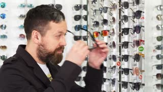 Profile shot of a bearded mature man trying on glasses in front of the mirror shopping for eyewear at the optometrist store consumerism retail customer eyes sight healthy vision.