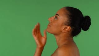 Profile studio portrait of a gorgeous African woman touching her neck sensually, smiling to the camera, posing on green chromakey. Mature gorgeous African female posing gracefully.