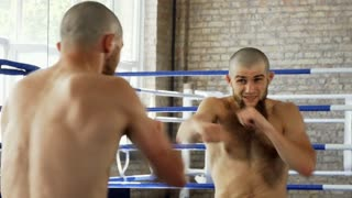 Rear view shot of a shirtless bearded male mma fighter training at the gym. Professional male boxer practicing punches in front of the mirror at the gym. Effort, agility, energy concept.