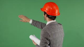 Rear view studio shot of a professional architect wearing hard hat moving objects on green chromakey screen. Male engineer working with futuristic technologies. Modern technology concept.