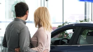 Rearview shot of a husband and wife choosing a new car at the dealership salon looking at the automobiles to buy buying shopping consumerism family transport travel anniversary