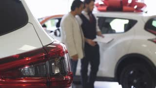 Selective focus on a car on the foreground, copy space. Professional salesman and his male client examining cars on the background. Businessman shopping for a new automobile.