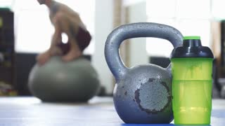 Selective focus on a kettlebell and bottle with water, copy space. Sportsman working out on the fitness ball on the background. Athletic man balancing on fit ball.