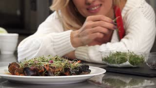 Selective focus on a plate with delicious mussels in tomato sauce decorated with greens beautiful mature woman cooking at home decorating dish with greens garnishing housewife eating.