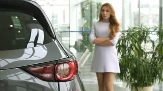 Selective focus on car lights gorgeous sexy woman in a dress looking at the auto thoughtfully decising which automobile to buy consumerism client customer purchasing sales rental retail