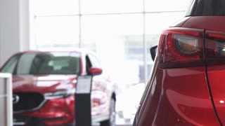 Selective focus on car lights on the foreground. Female customer examining cars for sale on the background. Woman shopping for a new vehicle. Buying cars concept. Driving automobile.