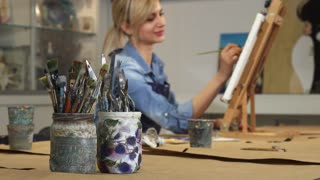 Selective focus on paintbrushes copy space professional female creative artist painter working on her painting on the background drawing artwork relaxation hobby lifestyle leisure design creative.
