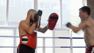 Shirtless muscular male kickboxer practicing his kicks and punches with the padman. Two strong athletic fighters training together, preparing for mixed martial arts competition.