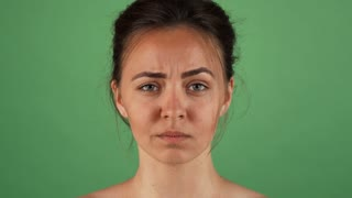 Shot of a beautiful young woman thinking, looking confused, posing on green chromakey background. Attractive female looking puzzled and doubtful. Decision making concept.