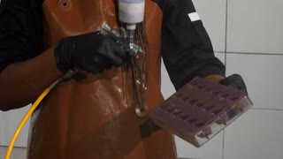 Shot of a female chocolatier decorating chocolate mold with airbrush, preparing to make chocolate candy. Cheerful African female confectioner making desserts at her kitchen.
