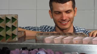 Shot of a handsome male chocolatier smiling joyfully examining freshly made chocolate candy he is selling. Happy confectioner smiling relaxing after cooking. Selling food concept.