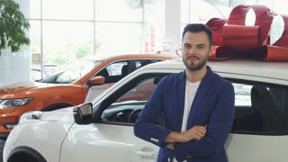 Shot of a handsome young man smiling joyfully, leaning on his new automobile, showing car keys to the camera. Ownership, driving, travelling concept. Man buying auto at the dealership.