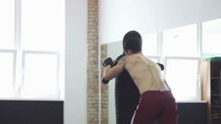 Shot of a muscular fighter practicing his punches at the gym. Powerful male athlete with ripped strong body training at sport studio. Champion preparing for mma competition.