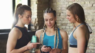 Shot of three female friends chatting after working out together. Fitness women using smart phone at the gym, relaxing after exercising. Friendship, communication, technology.