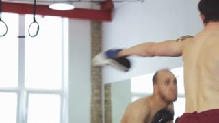 Shot of two athletic boxers training together at the gym. Strong male mma fighter boxing at the gym with his coach. Fighting, professional sports career. Masculinity, effort concept.