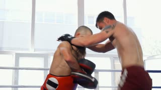 Shot of two powerful mixed martial arts athletes sparring in the boxing ring. Kickboxing coach holding pads during powerful training of an mma fighter. Sports, fighting, adrenaline.
