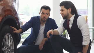 Shot of two young handsome men discussing an automobile for sale. Male friends examining wheels and tires of a new car at the dealership showroom. Friendship, lifestyle, vehicle.