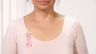 Sliding close up of a beautiful mature Asian woman smiling to the camera wearing pink ribbon breast cancer awareness consciousness prevention healthy patient medicine feminine