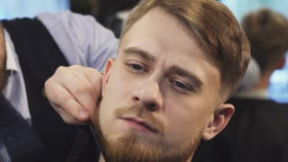 Sliding close up shot of a handsome young man getting his beard trimmed by a professional barber at the barbershop barbering styling profession occupation service lifestyle