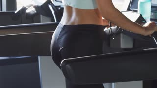 Sliding shot of a sexy young athletic woman with fit and toned body listening to music wearing earphones walking on the treadmill smiling to the camera over her shoulder sports motivation