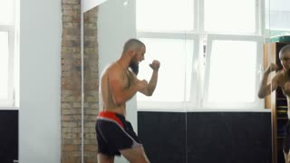 Sliding shot of a shirtless male boxer practicing his punches in sports studio in front of the mirror. Powerful male mma fighter training at the gym. Power, speed, motivation concept.