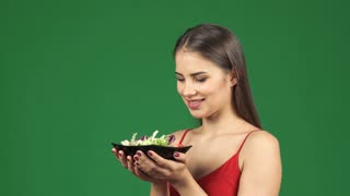 Studio close up of a beautiful healthy cheerful woman enjoying smelling tasty salad smiling happily to the camera health healthcare dieting weight loss fitness eating food vegetarian vegan.