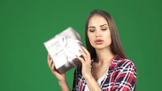 Studio close up of a gorgeous young happy woman smiling cheerfully shaking a gift box listening to it guessing what is her present on green chromakey background celebrating holidays emotions concept.