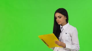 Studio portrait of a beautiful dark haired young businesswoman doing paperwork, looking away thougthfully. Attractive female worker filling documents on her clipboard. Employment concept.