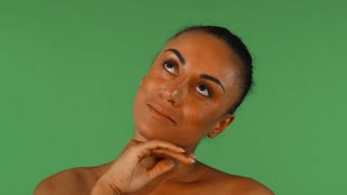 Studio portrait of a beautiful healthy and happy mature African woman touching her neck gently smiling to the camera. Gorgeous mulatto female posing sensually on chromakey.