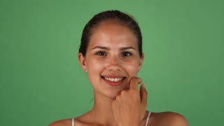 Studio portrait of a beautiful young woman with perfect unblemished skin smiling happily, looking to the side, posing on green background. Attractive female with flawless skin at studio.